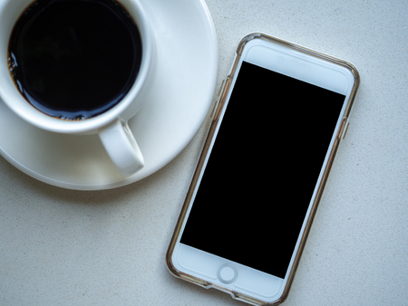 Blank  screen display of smartphone on table with coffee cup. Top view image of smartphone. Imagens