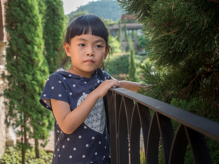 Portrait of a cute Asian small girl posing. Emotional image with space for text.