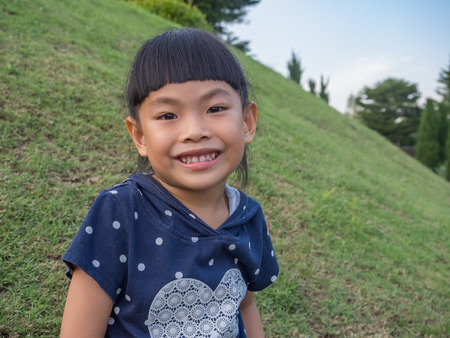 Smiley face Asian little girl in a park. Imagens