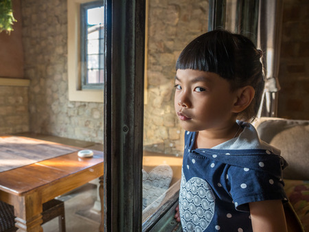 Moody and cute face of Asian little girl in resort room.