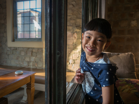 Happy face little Asian girl in a resort room.