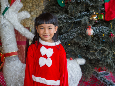 Portrait of little girl in Santa Claus cloth standing in front of decoration theme for Christmas.