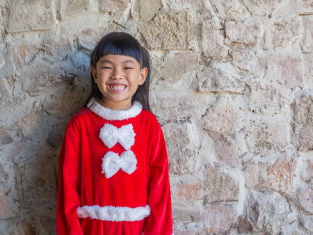 Portrait of little girl in Santa Claus cloth. Beautiful wall background.