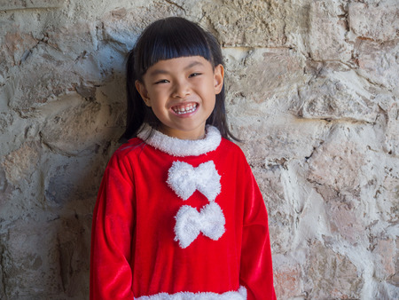 Portrait of big smile little girl in Santa Claus cloth in front of beautiful wall.