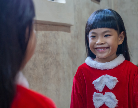 Little girl in Santa Claus cloth is smling to herself in a big mirror.