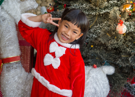 Portrait of little girl in Santa Claus cloth is posing with decoration theme for Christmas. Imagens