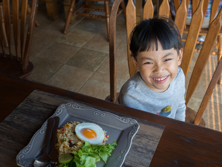 Asian small girl is smiling at a table in breakfast. Image is shot from above.