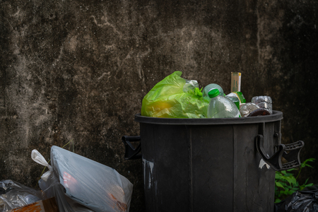 Overflowing trash can with plastic waste, wall background. Imagens