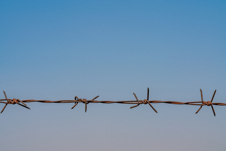 Close up rusty barbed wire fence in sky background
