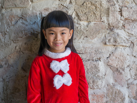 Portrait of little girl in Santa Claus cloth in front of beautiful wall. Imagens