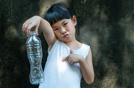 Child girl is holding with plastic bottle. Concept for stop using plastic.