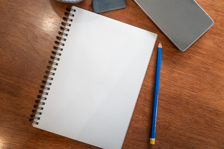 Blank notebooks page with pencil and eraser on a wood table