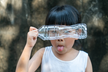 Child girl is acting with plastic bottle. Concept for stop using plastic. Imagens