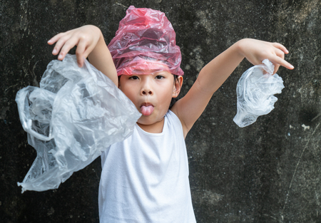 Cute child girl is holding plastic bags. Plastic is on her head. Concept for stop using plastic bag.