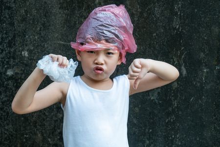 Cute child girl is posing with plastic bags. Plastic is on her head. Concept for stop using plastic bag.