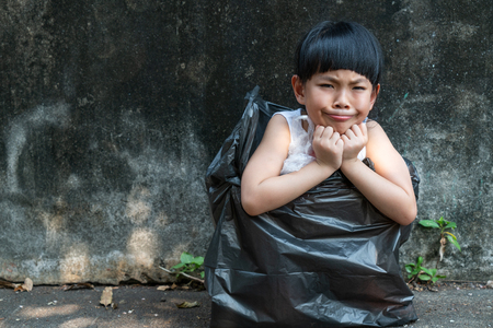 Little girl is showing worry face in garbage bag. Imagens