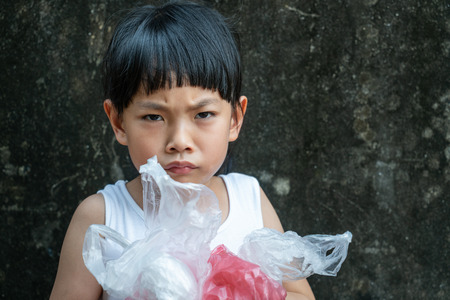 Asian little girl is holding plastic bags with her arms. Serious face about problem of plastic bag for her generation.