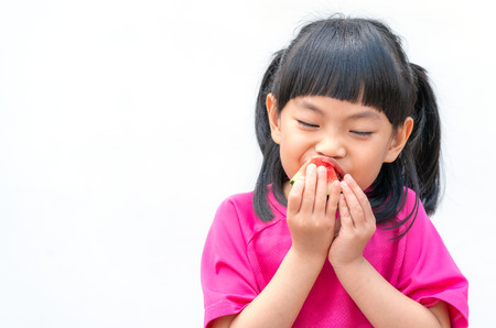 Asian little girl is eating a slice of watermelon, white wall background.