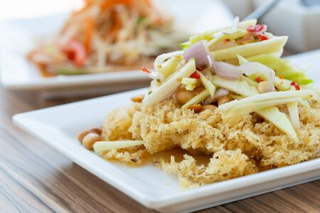 Healthy Thai Food, spicy salad with crispy fried catfish or Yum Pla Dook Fu in Thai food menu.