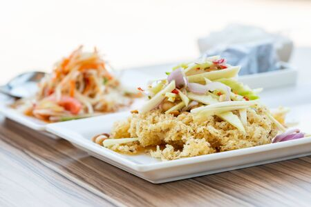 Healthy Thai Food, spicy salad with crispy fried catfish or Yum Pla Dook Fu in Thai food menu. Bright light background
