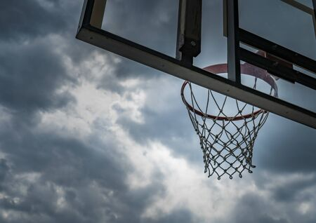 Basketball hoop against cloudy sky before rain with copy space.
