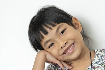 Close up face of Asian little girl, smiling face, relax. Image on white background.