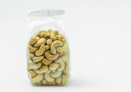 Cashew nuts in plastic bag on  white background. Front side, space for label. Stock Photo