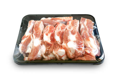 Isolated organic spare ribs in black tray container, plastic film wrapped, white background. Soft part of pork spare ribs. Fresh raw spare ribs arranged in small tray for sell.