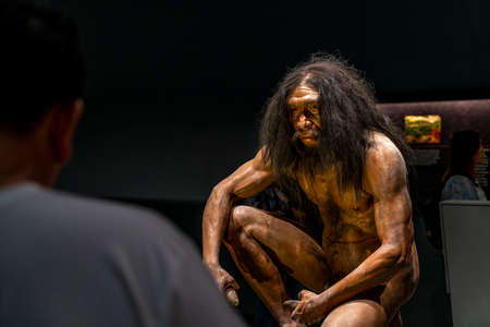 Pathumthani, Thailand - Dec 31, 2020 Realistic model of Prehistoric human sitting, holding stone at Praram nine museum or National Science Museum, the biggest museum of Thailand. 新聞圖片