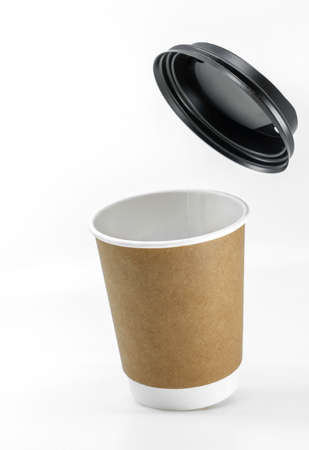 Close up slightly tilted coffee paper cup or take out coffee paper cup with lid flying on the top. Image on white background. Blank space for design and branding.