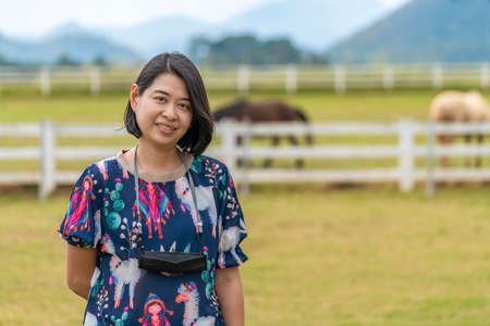 Portrait of Asian middle-aged tourist woman in farm of Thailand, having medical mask hang on neck with strap. Blurred background of farm, animal and nature. Concept for travel while covid-19 epidemic.