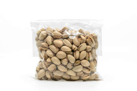 Pistachios in cleared plastic bag packaging for sale on white background. Isolated plastic bag of pistachios with clipping path. Front view, blank space for label branding design.