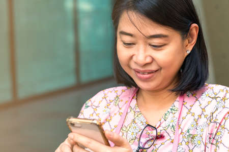Portrait Asian middle-aged woman, close up Asian woman with smiling face while looking at her cellphone, wearing casual, hang eyeglasses on tee shirt's neck. Asian woman with short black hair.