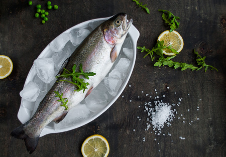 Fresh trout on ice with salad rocket, green peas, sea salt, lemon on dark wooden table photo