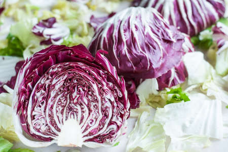 horisontal: Sliced radicchio on table with green salad. Horisontal