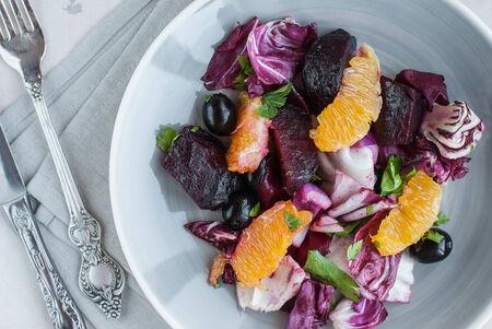 salad plate: Remolacha fresca, naranja, radicchio, aceitunas negro ensalada. De cerca Foto de archivo