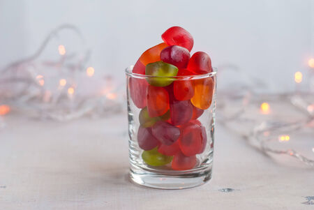 horisontal: Colorful sweet jellies in a glass on a white wooden table with garland lights. Selective focus. Horisontal