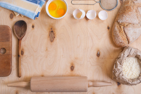 Baking light warm background with cutting board, eggshell, bread, flour, rolling pin. Vintage wood table from above. Rustic background with free text space. Stock Photo