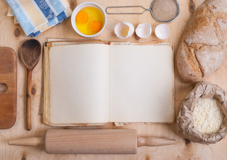 Baking light warm background with blank cook book, cutting board, eggshell, bread, flour, rolling pin. Vintage wood table from above. Rustic background with free text space. Foto de archivo
