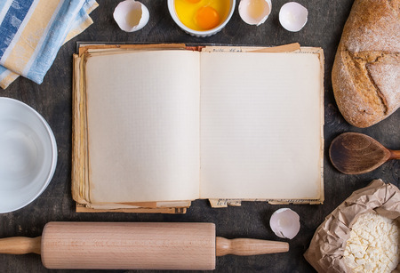 Baking dark background with blank cook book, eggshell, bread, flour, rolling pin. Vintage wood table from above. Rustic background with free text space.