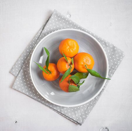 polka dot fabric: Clementine tangerines with green leaves on white wooden background in a gray bowl. From above. Grey polka dot fabric