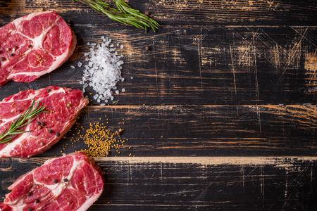 Raw juicy meat steak on dark wooden background 스톡 콘텐츠