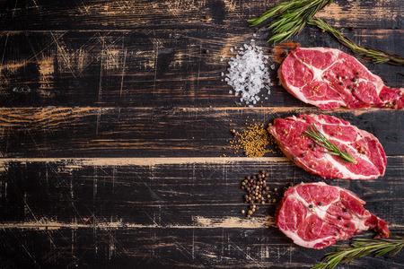 meat grill: Raw juicy meat steak on dark wooden background Stock Photo