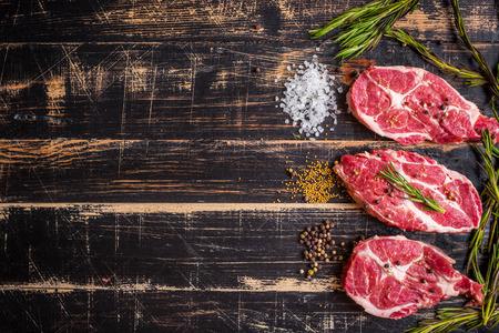 Raw juicy meat steak on dark wooden background photo
