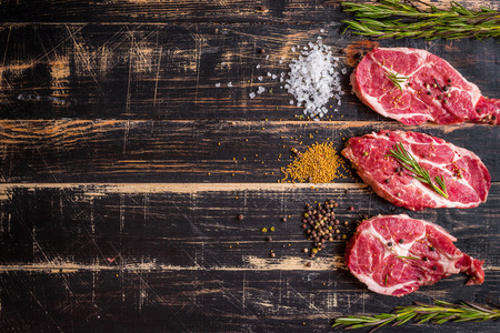 Raw juicy meat steak on dark wooden background Фото со стока
