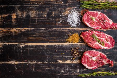 Raw juicy meat steak on dark wooden background Stockfoto