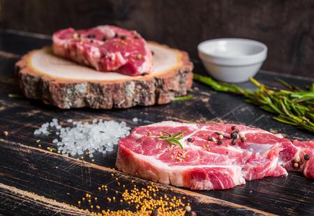 Raw meat steak on dark wooden background ready to roasting photo