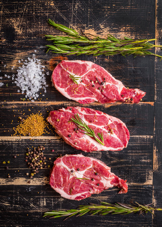 Raw juicy meat steak on dark wooden background 版權商用圖片