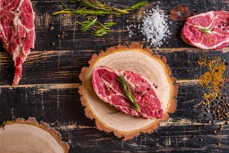 Raw juicy meat steak on dark wooden background Foto de archivo