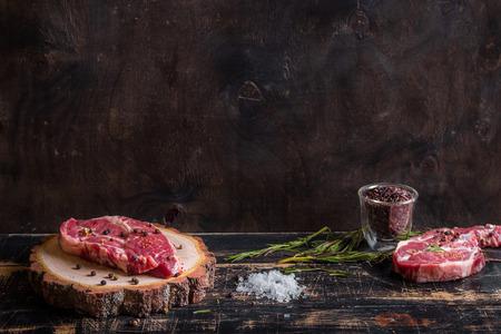 carnes rojas: Filete de carne cruda en el fondo de madera oscura listo para tostado